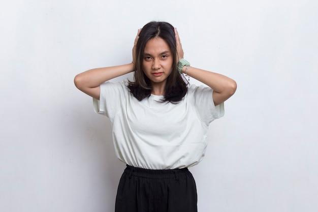 Junge asiatische schöne frau, die beide ohren mit den händen bedeckt, die auf weißem hintergrund lokalisiert werden