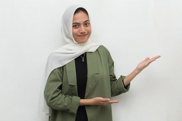 Junge asiatische schöne frau, die hijab lächelnd selbstbewusstes zeigen mit den fingern in verschiedene richtungen trägt