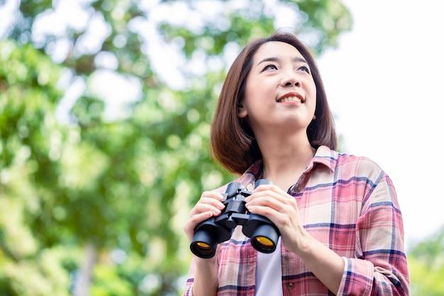 Junge asiatische schöne frau, die natürlich schaut und fernglas im öffentlichen park mit einem glücklichen gesicht steht und lächelt