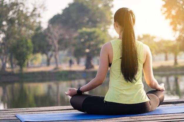Junge asiatische schöne frau, die yoga praktiziert und morgens im lotussitz im freien neben dem see meditiert, um sich zu entspannen und zu beruhigen. harmonie- und meditationskonzept. gesunder lebensstil