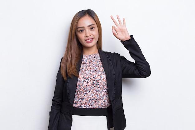 Junge asiatische schöne geschäftsfrau mit ok zeichen geste tumb up isoliert auf weißem hintergrund