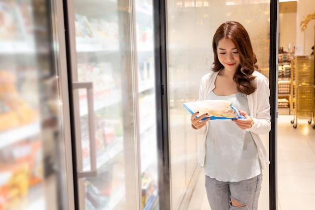 Junge asiatische schöne haltende tiefkühlkost am kühlschrank im supermarkt. auswahl von fertiggerichten im einkaufszentrum