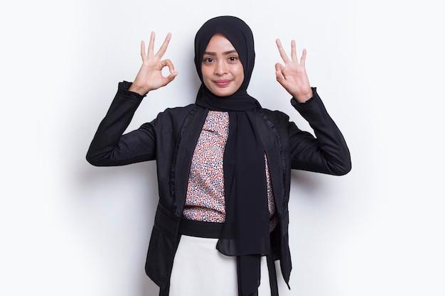 Junge asiatische schöne muslimische frau mit ok-zeichen-geste-tumb-up isoliert auf weißem hintergrund