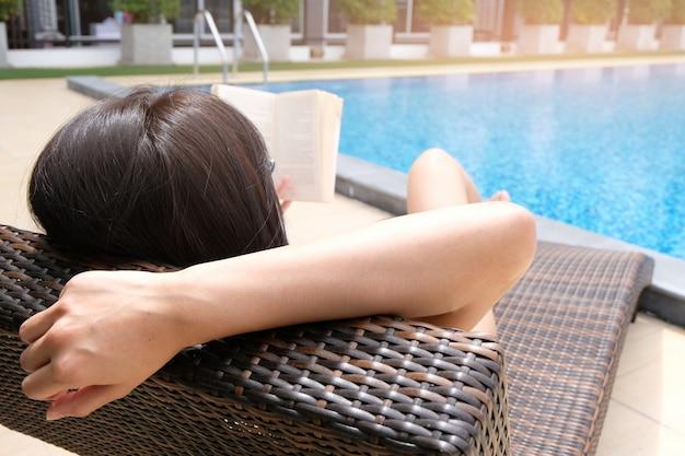 Junge asiatische schönheit, die im swimmingpool liegt auf einem sonnenruhesessel am badekurort sich entspannt
