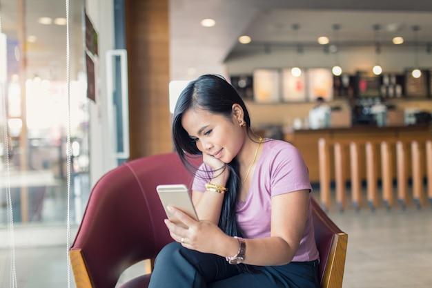 Junge asiatische schönheit, die intelligentes telefon in der kaffeestube verwendet.
