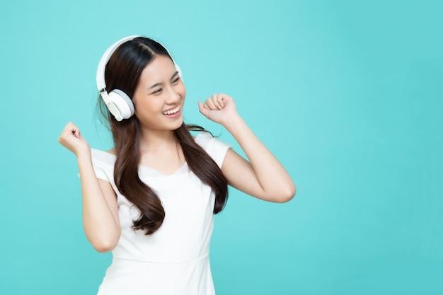 Junge asiatische schönheitsfrau, die musik mit kopfhörern in wiedergabelisten-liedanwendung auf smartphone lokalisiert auf grüner wand hört