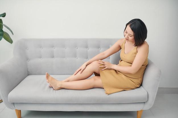 Junge asiatische schwangere frau, die auf sofa sitzt und fußschmerzen und beinkrämpfe auf ihrem letzten trimester hat.