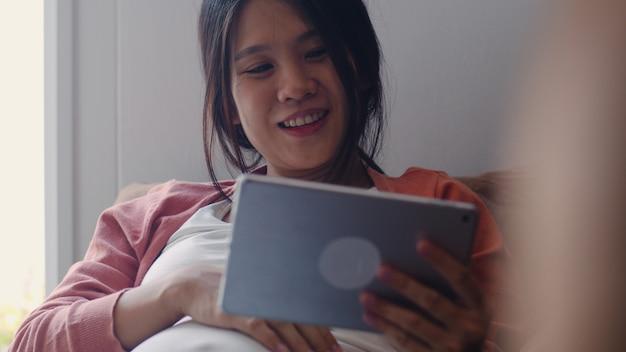 Junge asiatische schwangere frau, die tablettensuchschwangerschaftsinformationen verwendet. die mutter, die das glückliche lächeln positiv und ruhig sich fühlt, während mach s gut ihr kind, das zu hause auf sofa im wohnzimmer liegt.