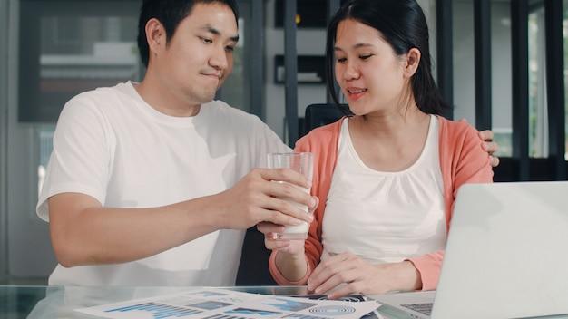 Junge asiatische schwangere frau, die zu hause laptopaufzeichnungen des einkommens und der ausgaben verwendet. vati, der seiner frau milch während rekordbudget, steuer, finanzdokument morgens bearbeitet im wohnzimmer am haus gibt.