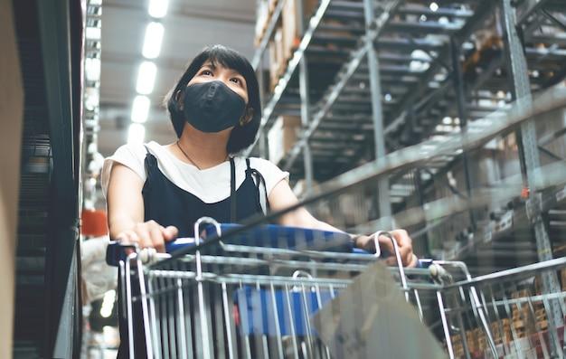 Junge asiatische schwangere frau mit einkaufswagen am supermarkt