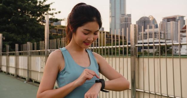 Junge asiatische sportlerin übt das überprüfen des fortschritts aus, der herzfrequenzmonitor auf smartwatch in der stadt schaut. teen girl runner ruht erschöpft nach intensivem lauftraining cardio am morgen.