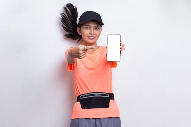 Junge asiatische sportliche frau, die handy auf weißem hintergrund demonstriert