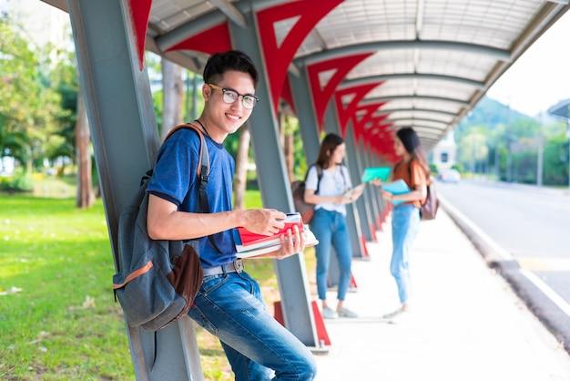Junge asiatische studenten, die nachhilfe und lesebuch am gehweg in der universität unterrichten