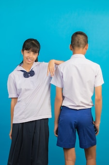 Junge asiatische studenten und asiatische männliche studenten stehen zusammen auf einem blau.