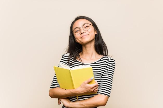 Junge asiatische studentin, die ein buch hält, das lacht und spaß hat.