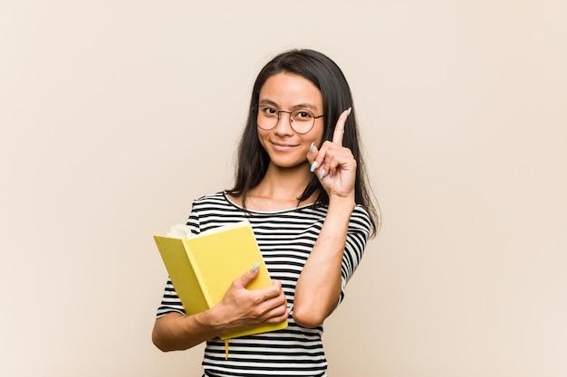 Junge asiatische studentin, die ein buch hat irgendeine großartige idee, konzept der kreativität hält.