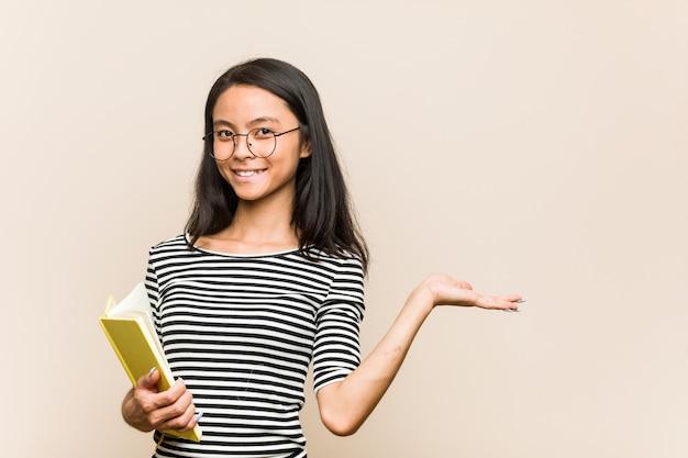 Junge asiatische studentin, die ein buch zeigt einen kopienraum auf einer palme hält und eine andere hand auf taille hält.