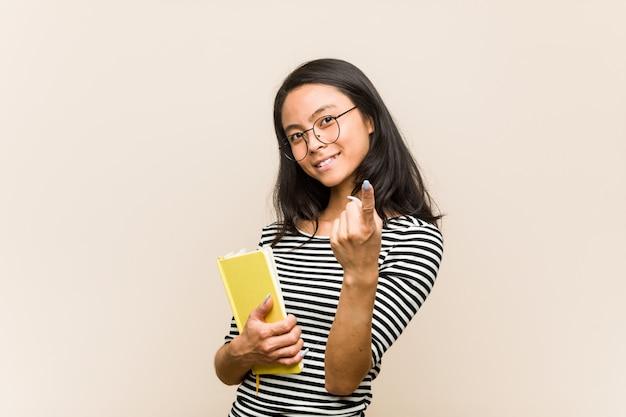 Junge asiatische studentin, die ein buch zeigt mit dem finger auf sie hält, als ob einladung näher kommen.
