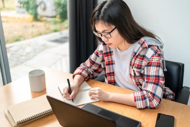 Junge asiatische studentin, die von zu hause aus während der sperrung der stadt aufgrund der ausbreitung des koronavirus arbeitet und studiert