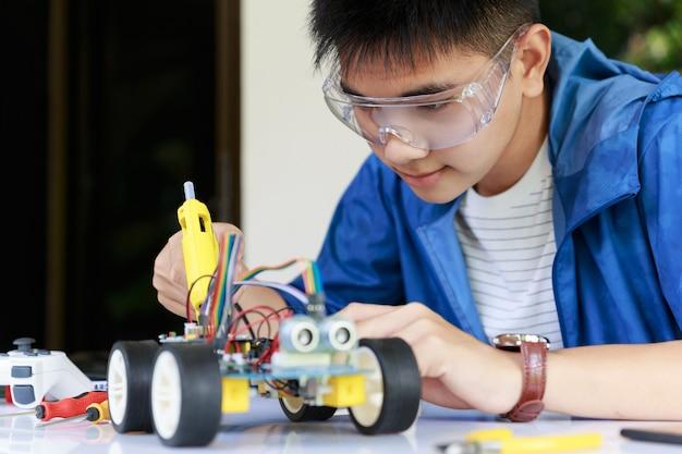 Junge asiatische teenager, die energie- und signalkabel an sensorchip der spielzeugautowerkstatt verstopfen.