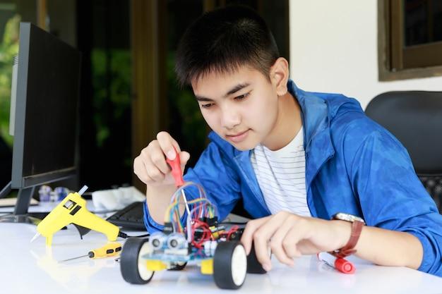 Junge asiatische teenager genießen mit spielzeugauto-werkstatt.