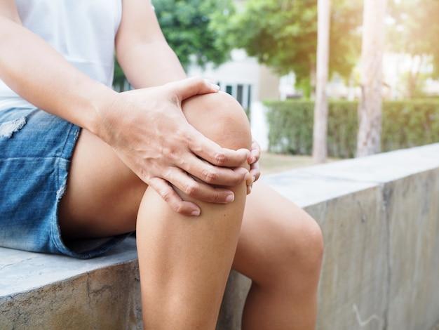 Junge asiatische thailändische frauen mit körperschmerzen, die muskelverletzung mit knieschmerzen und beinschmerzen leiden.
