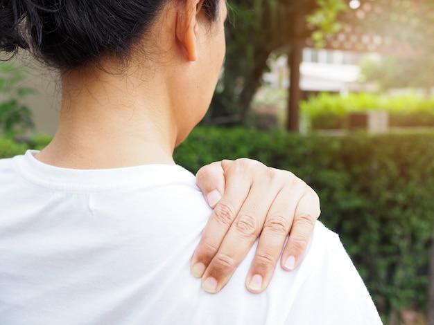 Junge asiatische thailändische frauen mit körperschmerzen, die muskelverletzung mit schulterschmerzen und rückenschmerzen leiden.