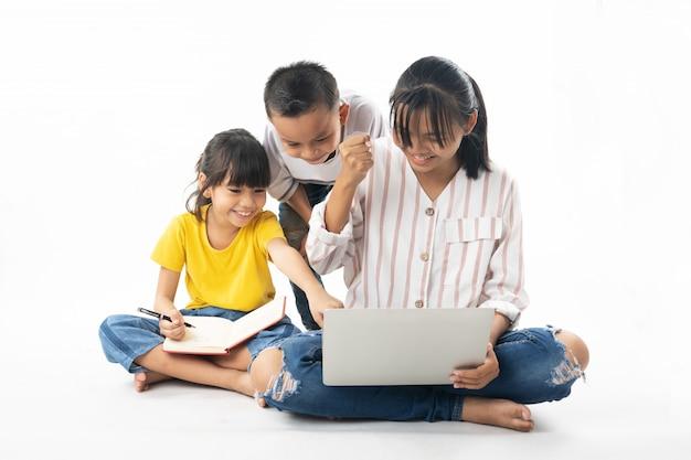 Junge asiatische thailändische kinder, junge und mädchen, die auf laptop durch technologie und multimedia lernen und schauen