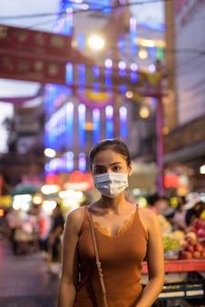 Junge asiatische touristenfrau, die maske zum schutz vor ausbruch des koronavirus in chinatown bei nacht trägt