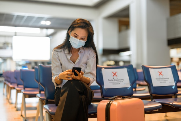 Junge asiatische touristenfrau mit maske unter verwendung des telefons und sitzend mit abstand am flughafen