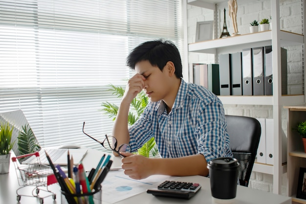 Junge asiatische unternehmen haben kopfschmerzen und sind bei der arbeit krank