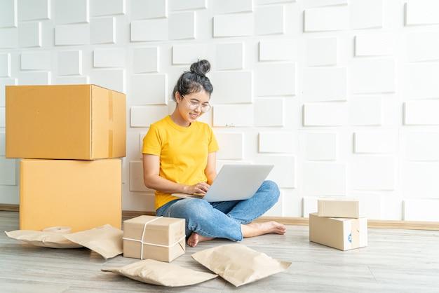 Junge asiatische unternehmen starten online-verkäufer besitzer mit computer für die überprüfung der kundenbestellungen per e-mail oder website und vorbereitung von paketen