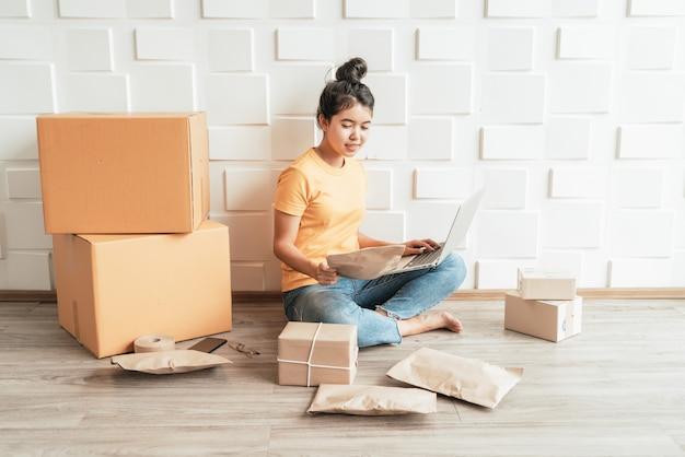 Junge asiatische unternehmen starten online-verkäufer besitzer mit computer für die überprüfung der kundenbestellungen von e-mail oder website und vorbereitung von paketen