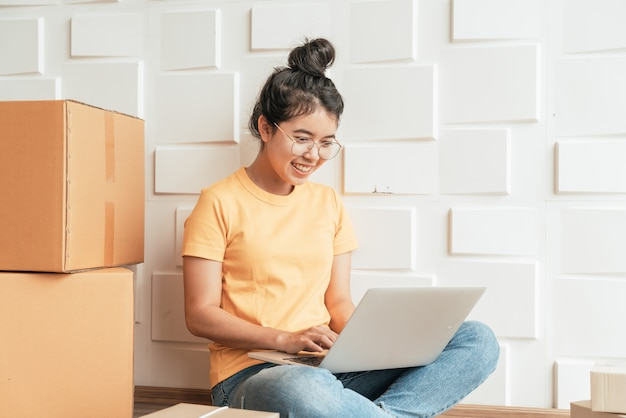 Junge asiatische unternehmen starten online-verkäufer besitzer mit computer, um die kundenbestellungen per e-mail oder website zu überprüfen und pakete vorzubereiten