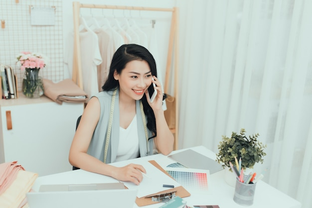 Junge asiatische unternehmerinnen / modedesignerin, die an ihrem atelier arbeiten