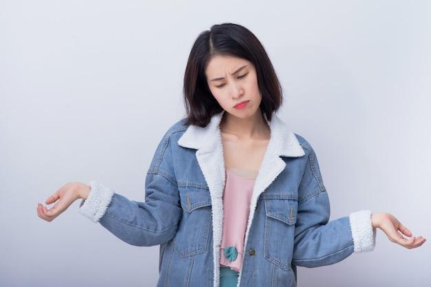 Junge asiatische verärgerte frau, die negative und schlechte emotion trägt, die blaues freizeitkleidungsporträt trägt