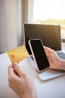 Junge asiatische verbraucherfrauenhand, die eine kreditkarte hält