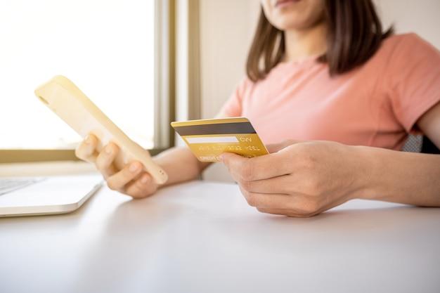 Junge asiatische verbraucherfrauenhand, die eine kreditkarte und ein smartphone hält, um online einzukaufen