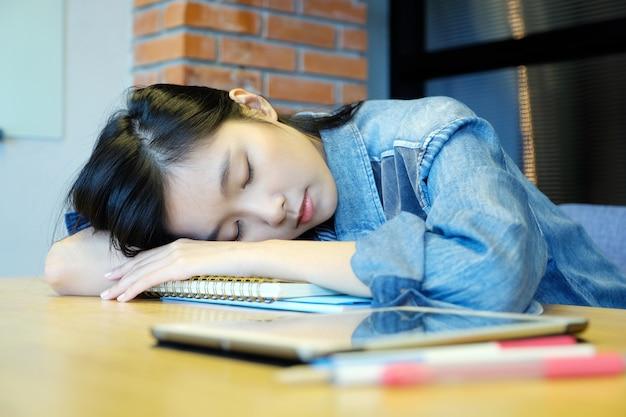 Junge asien-frau, die wie erschöpft von der arbeit mit laptop-computer an ihrem büro des schläft