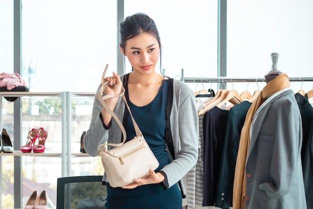 Junge asien-schönheit leben videoblog (vlogger) und verkaufstasche im on-line-e-commerce-einkaufen am kleidungsshop.