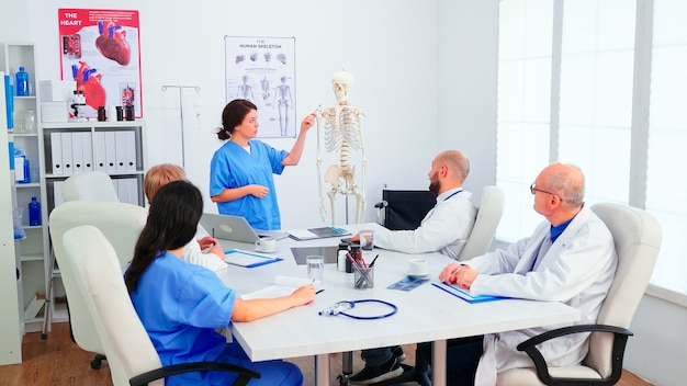 Junge assistentin zeigt auf skelett vor ärzten im konferenzraum. klinik-expertentherapeut im gespräch mit kollegen über krankheit, mediziner