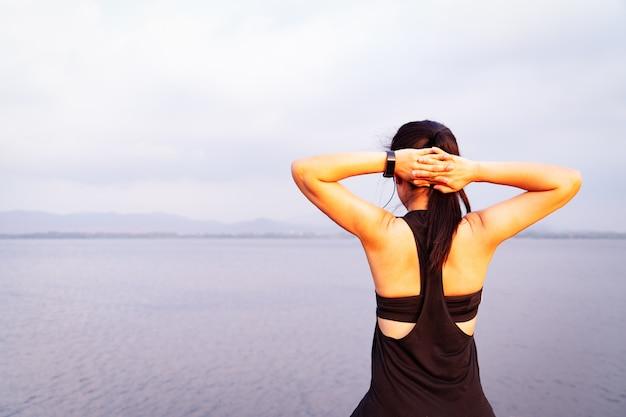 Junge athletenfrau, die nahe dem see im freien ausdehnt