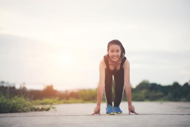 Junge athletenfrau ist bereit, lauf zu beginnen oder zu rütteln