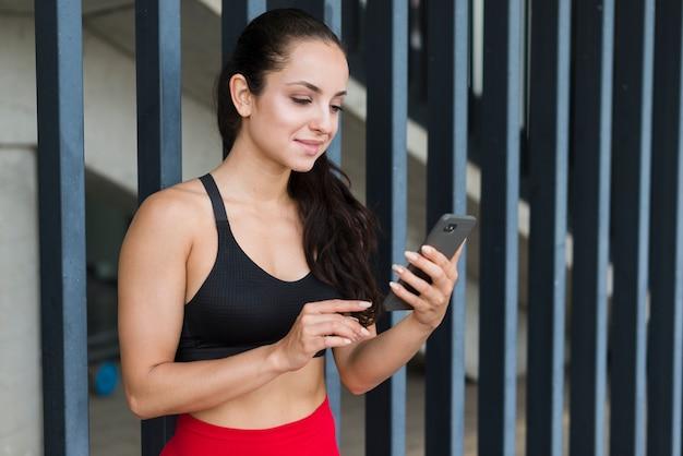 Junge athletenfrau mit einem smartphone