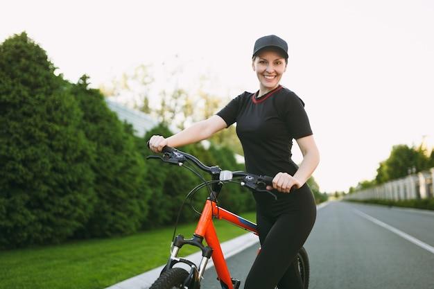 Junge athletische brünette starke frau in schwarzer uniform, kappenstopp, straße auf schwarzem fahrrad mit orangefarbenen elementen im freien an sonnigen frühlings- oder sommertagen zu fahren. fitness, sport, gesundes lifestyle-konzept.