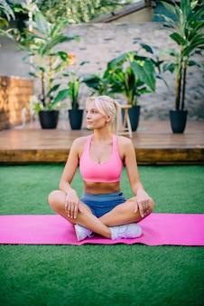 Junge athletische frau, die am sommertag auf yogamatte im hof sitzt