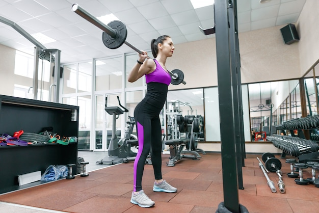 Junge athletische frau, die auf den maschinen in der modernen sportturnhalle trainiert