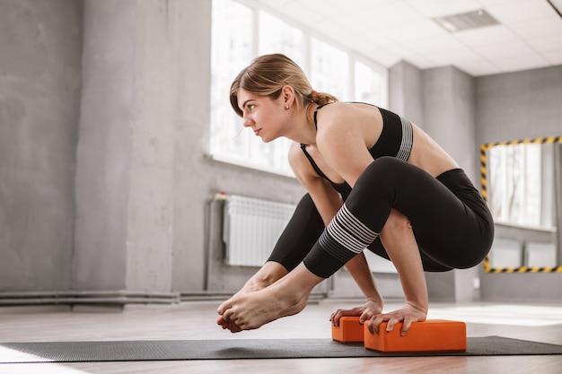 Junge athletische frau, die auf ihren händen balanciert und yoga praktiziert