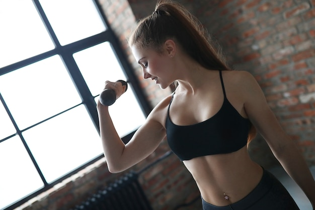 Junge athletische frau, die ihre übungsroutine zu hause tut