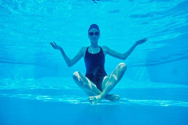 Junge athletische frau, die im lotussitz unter wasser im schwimmbad sitzt